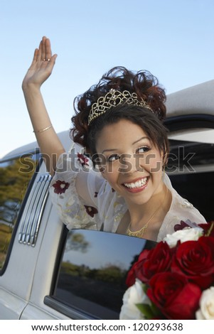 Happy  bride waving hand while sitting in the car on a wedding day - stock photo