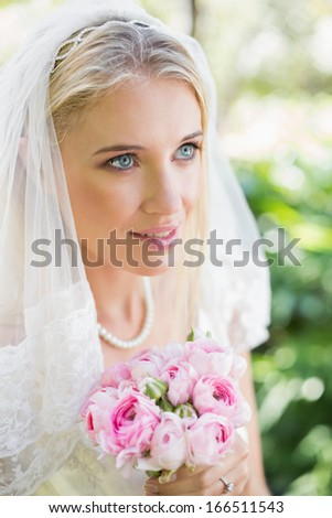 Happy bride wearing veil holding bouquet looking away in the countryside