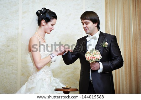 Happy bride wears wedding ring her groom. Solemn registration of marriage. - stock photo