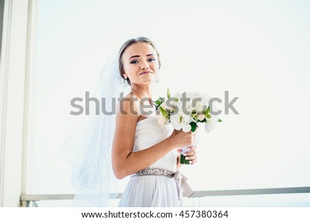 Happy bride with flowers looking at photographer