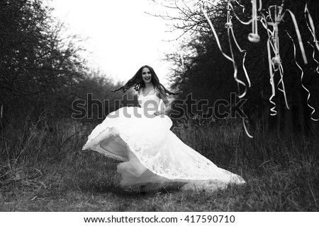 Happy bride with in white wedding dress dancing outdoor near trees with decorative ribbons, black and white