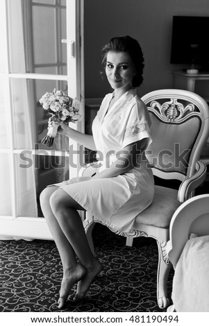 Happy bride with lovely bouquet on white chair