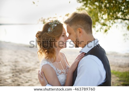 happy bride with wreath  and groom near the sea on their wedding