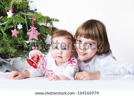 Happy brother and baby sister playing together under a Christmas tree - stock photo