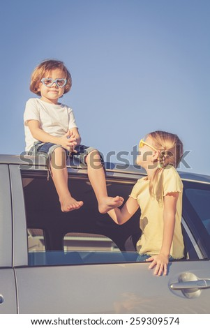 Happy brother and sister are sitting in the car at the day time - stock photo