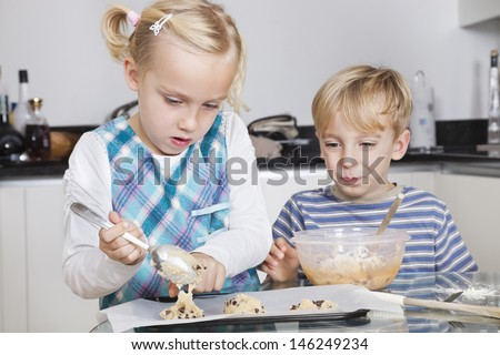 Happy brother and sister baking cookies in kitchen - stock photo