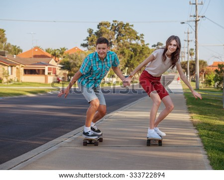 Happy brother and sister having fun with  skateboard on the street in the evening light - stock photo