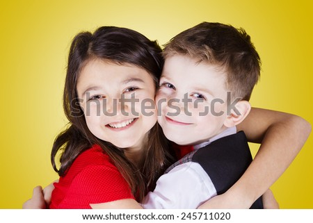 Happy brother and sister hugging over yellow background.Love ,Family,Friendship - stock photo