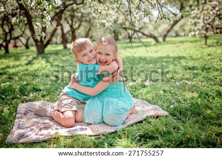 happy brother and sister hugs and having fun in spring apple garden