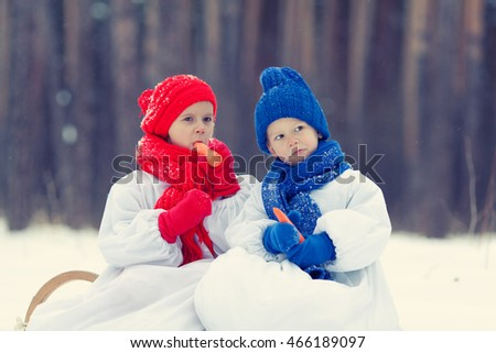 Happy brother and sister in costumes snowman walking in winter forest, outdoor