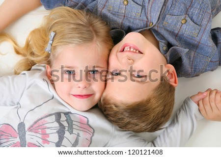 Happy Brother and Sister laying on the floor - stock photo