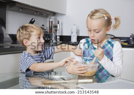 Happy brother and sister mixing batter together in kitchen - stock photo