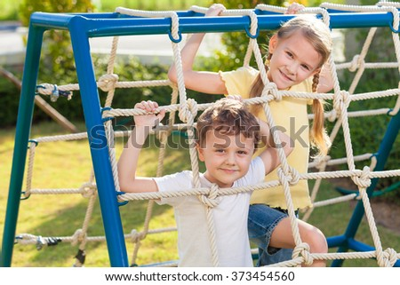 happy brother and sister playing on the playground at the day time - stock photo