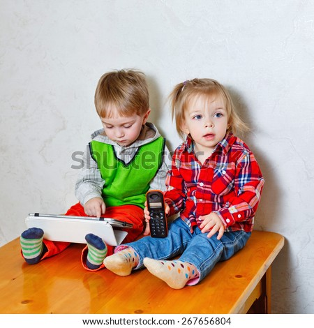 Happy brother and sister sitting on the kitchen table. Little cute girl holding in her hands a radiotelephone, and boy holding a tablet computer. Love, Family, Friendship - stock photo
