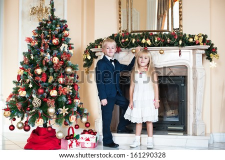 Happy brother and sister standing near the fireplace and a Christmas tree. children waiting for the new year - stock photo