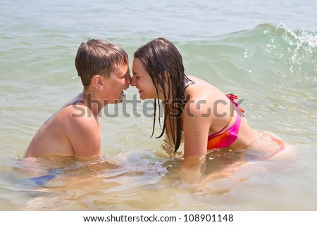 Happy brother and sister swim in the sea - stock photo