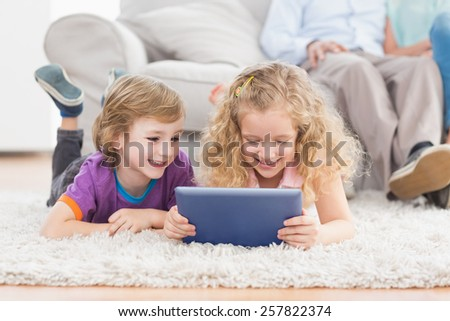 Happy brother and sister using digital tablet while lying on rug at home - stock photo