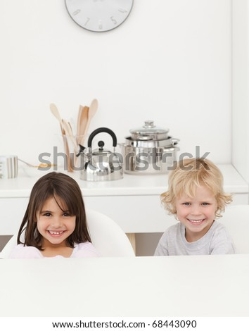 Happy brother and sister waiting their breakfast sitting in the kitchen - stock photo