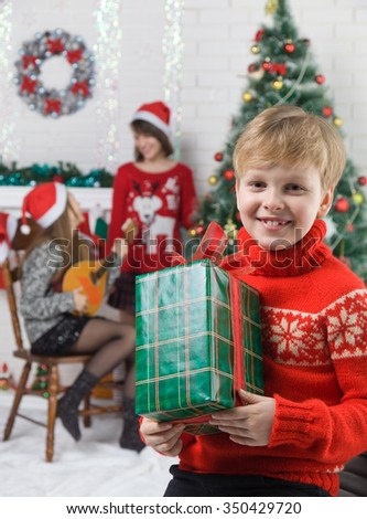 Happy brother and sisters is near the fireplace and a Christmas tree. children waiting for the new year - stock photo