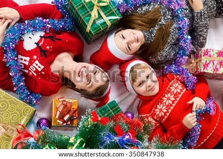 Happy brother and sisters lying near a Christmas tree. children waiting for the new year - stock photo