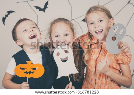 Happy brother and two sisters on Halloween party - stock photo