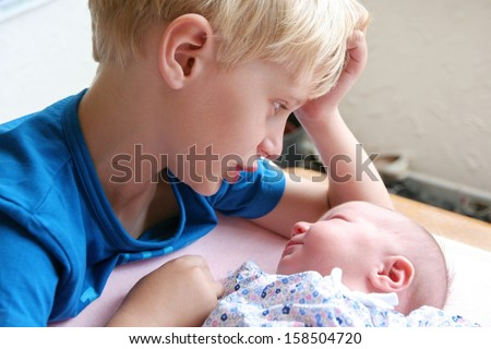 Happy brother enjoys time together with his little newborn baby sister looking at her tender while she sleeps - stock photo
