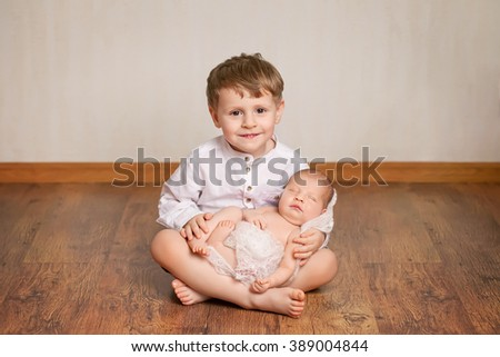 Happy brother holding his newborn baby sister - stock photo
