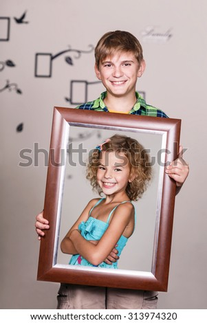 Happy brother holding portrait with his sister each is located inside her own frame  - stock photo