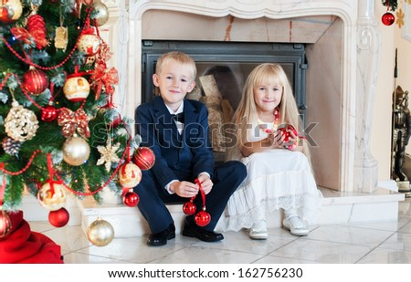 happy brother sister in evening dresses in anticipation of new year near the tree - stock photo