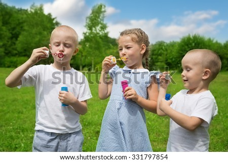 Happy brothers and sister inflate soap bubbles outdoors in park - stock photo