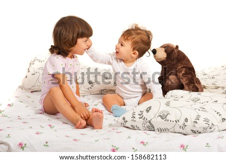 Happy brothers in bed standing together against white background