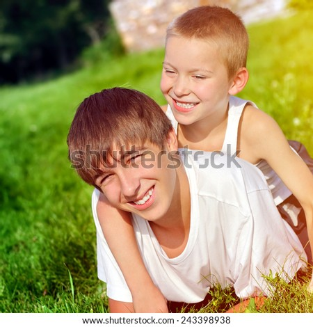 Happy Brothers on the Grass in the Summer Park - stock photo