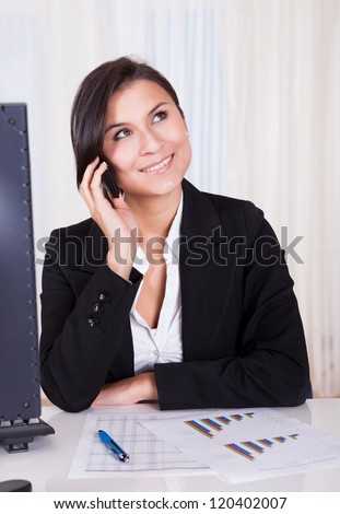 Happy brunette business woman listening to someone on her mobile phone
