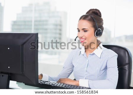 Happy brunette businesswoman using headset in bright office - stock photo