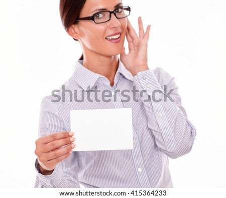 Happy brunette businesswoman with glasses, toothy smile, wearing her long hair tied back, and a button down shirt, holding a blank copy space in one hand gesturing her surprise with the other hand