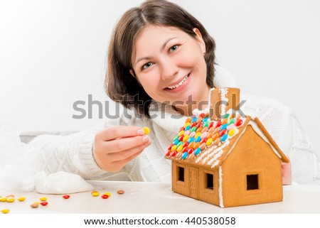 happy brunette decorated with festive a gingerbread house