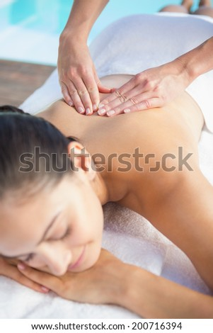 Happy brunette enjoying a massage poolside outside at the spa - stock photo