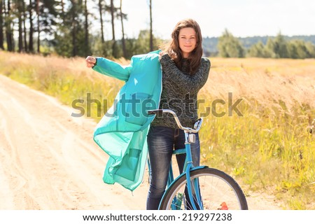 Happy brunette girl during cycling on dirt road - stock photo