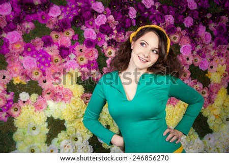 Happy brunette girl smiling wearing in green dress with pink and yellow flowers background  - stock photo
