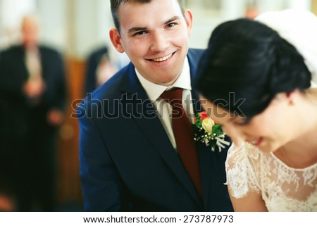 happy brunette groom in blue suit posing smiling