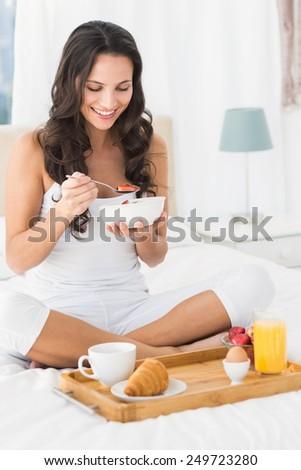 Happy brunette having breakfast in bed at home in bedroom - stock photo