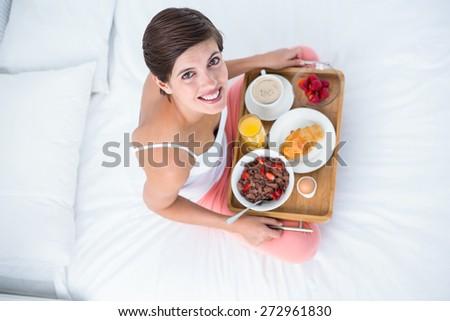 Happy brunette having her breakfast in bed at home in he bedroom - stock photo