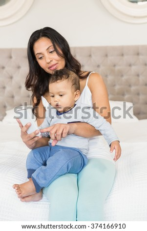 Happy brunette holding her baby and using smartphone in bedroom