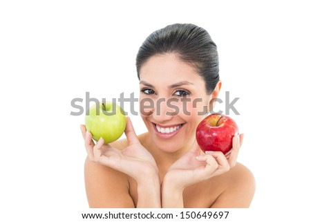 Happy brunette holding red and green apples and looking at camera on white background