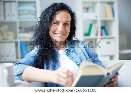 Happy brunette in casual clothes reading book at home