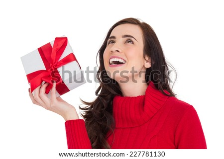 Happy brunette in red jumper hat showing a gift on white background - stock photo