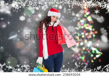 Happy brunette in winter wear holding shopping bags against shimmering christmas tree of lights - stock photo