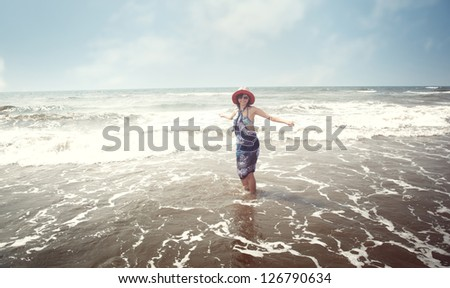 Happy brunette lady with hat and sunglasses standing at the beach