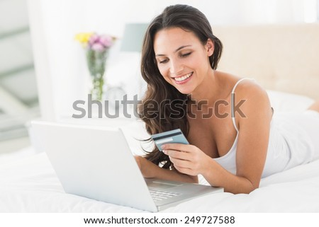 Happy brunette shopping online with laptop at home in bedroom - stock photo