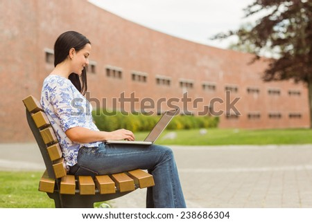 Happy brunette sitting on bench typing on laptop in the park - stock photo